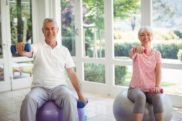 Älteres paar, das mit hanteln auf übungsball trainiert