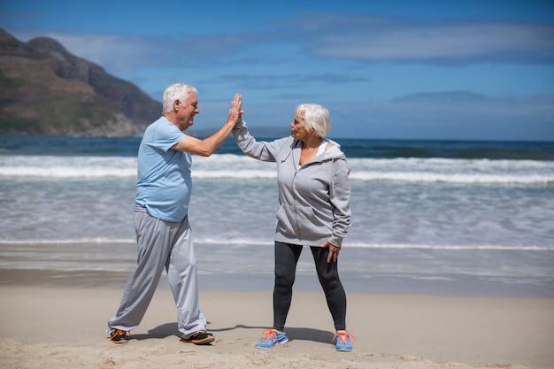 Älteres paar, das nach dem training am strand high five gibt