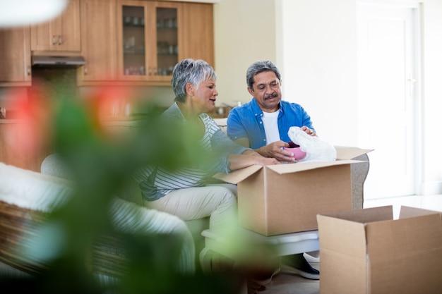 Älteres paar, das pappkarton im wohnzimmer auspackt