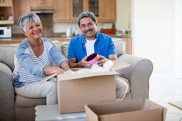 Älteres paar, das pappkarton im wohnzimmer zu hause auspackt