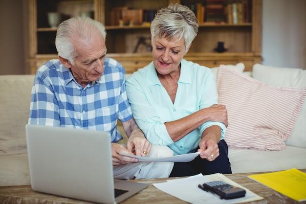Älteres paar, das rechnungen im wohnzimmer überprüft