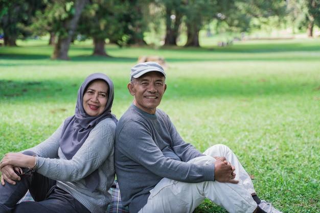 Älteres paar, das rücken an rücken sitzt, während es sich im park entspannt