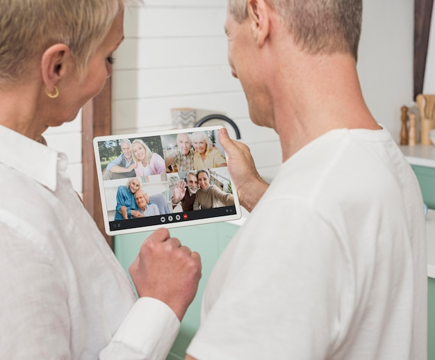 Älteres paar, das seine freunde per videoanruf anruft