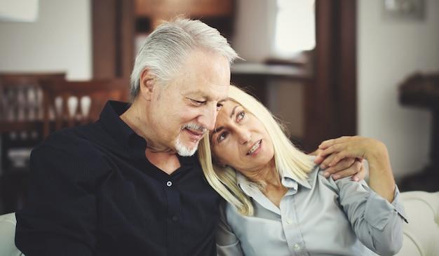 Älteres paar, das sich auf einem sofa entspannt und miteinander spricht