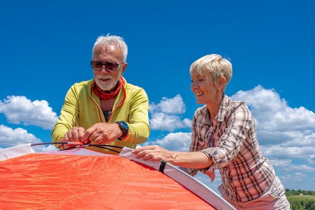 Älteres paar, das sich auf ruhe vorbereitet und ein zelt aufbaut