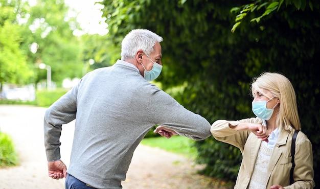 Älteres paar, das sich mit dem ellbogen trifft und begrüßt