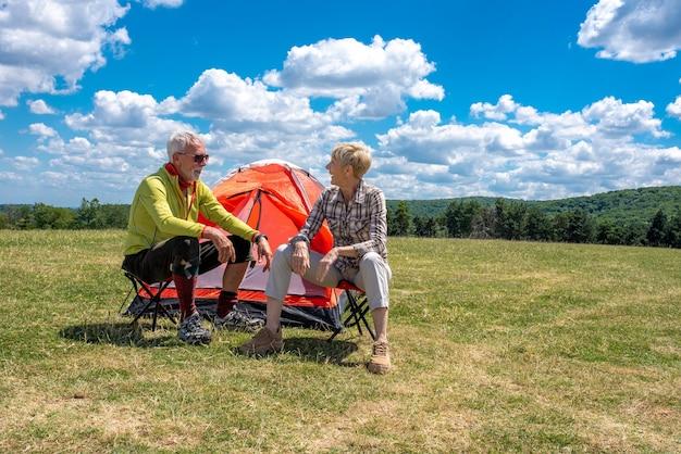 Älteres paar, das sich mit einem zelt auf dem feld ausruht