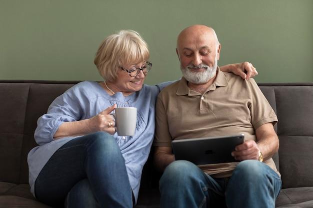 Älteres paar, das tablettenmittelschuss betrachtet