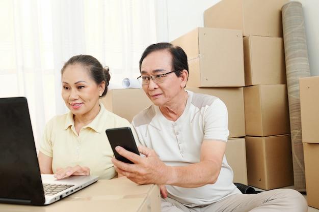 Älteres paar, das umzugsunternehmen bestellt