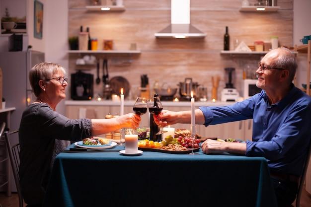 Älteres paar, das während des abendessens gläser mit rotwein röstet. älterer mann und frau sitzen am tisch in der küche, reden, genießen das essen, feiern ihr jubiläum im esszimmer.