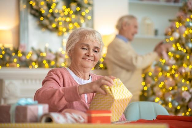 Älteres paar, das weihnachtsgeschenke vorbereitet und weihnachtsbaum verziert