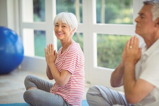 Älteres paar, das yoga auf übungsmatte durchführt