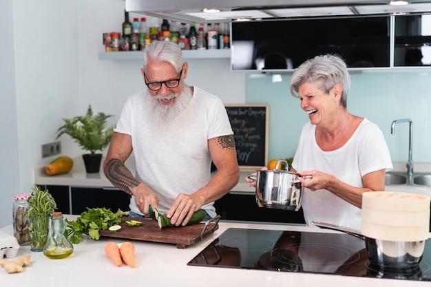 Älteres paar, das zu hause kocht, während vegetarisches mittagessen vorbereitet