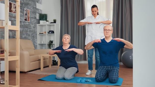 Älteres paar, das zu hause physiotherapie mit arzt macht. haushaltshilfe, physiotherapie, gesunder lebensstil für ältere menschen, training und gesunder lebensstil