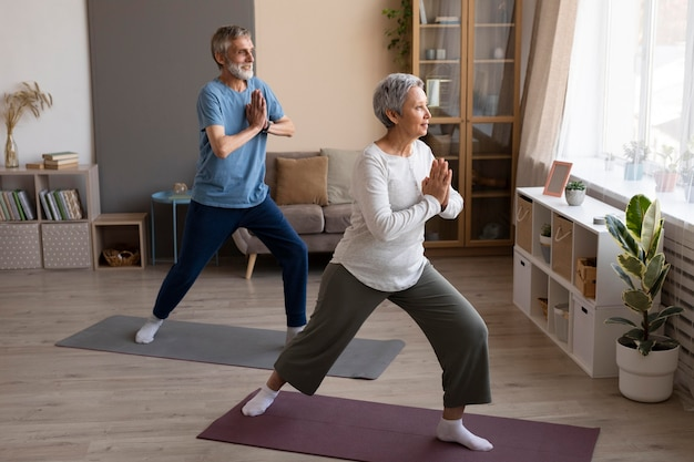 Älteres paar, das zu hause yoga praktiziert