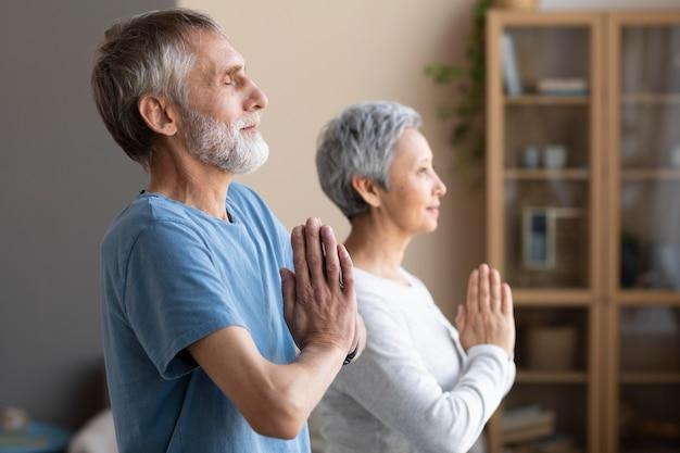 Älteres paar, das zu hause zusammen trainiert