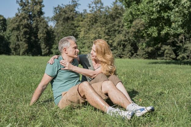 Älteres paar, das zusammen auf gras sitzt