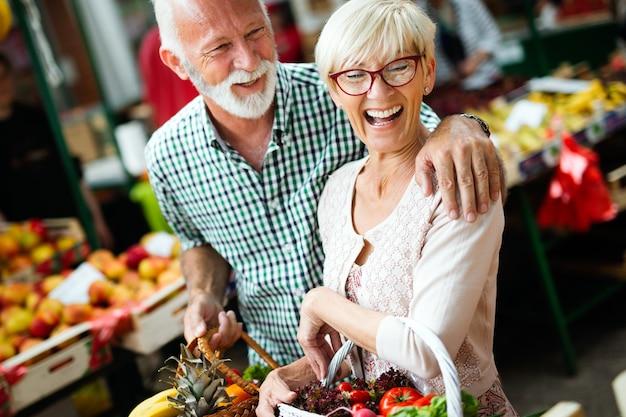 Älteres paar einkaufen von gemüse und obst auf dem markt. gesunde ernährung.