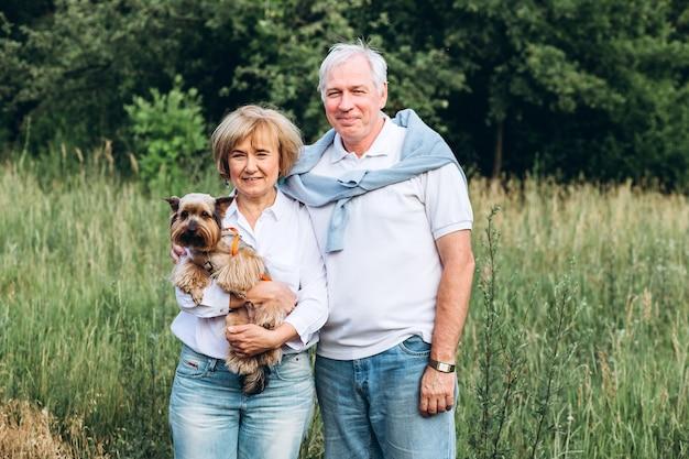 Älteres paar geht mit kleinem hund in der natur spazieren