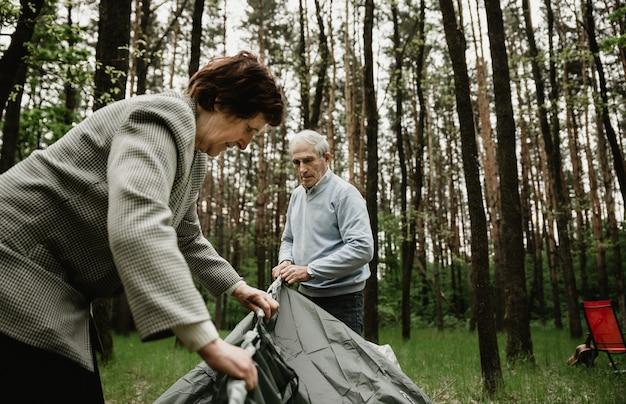 Älteres paar genießt urlaub und baut das zelt auf. erwachsene verbringen sommerferien in der natur und schlagen ein zelt auf. senioren campen und bauen zelt auf