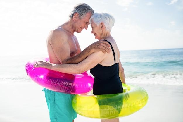 Älteres paar im aufblasbaren ring, der sich umarmt