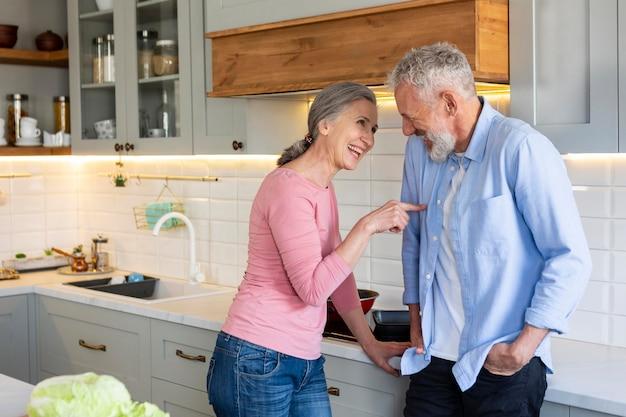 Älteres paar in der küche mit mittlerem schuss des essens
