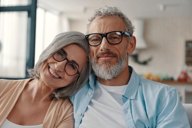 Älteres paar in freizeitkleidung lächelt und schaut in die kamera, während es zeit zu hause verbringt