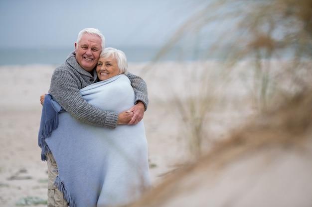 Älteres paar in schal am strand gewickelt