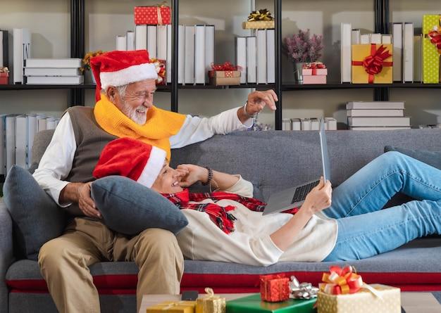 Älteres paar in weihnachtsmütze, das auf der sofacouch sitzt und sich auf dem rundenvideo mit der familie online über einen laptop-computer zu hause mit weihnachtsbaum anruft. in den ferien kontakt zu den enkeln halten.