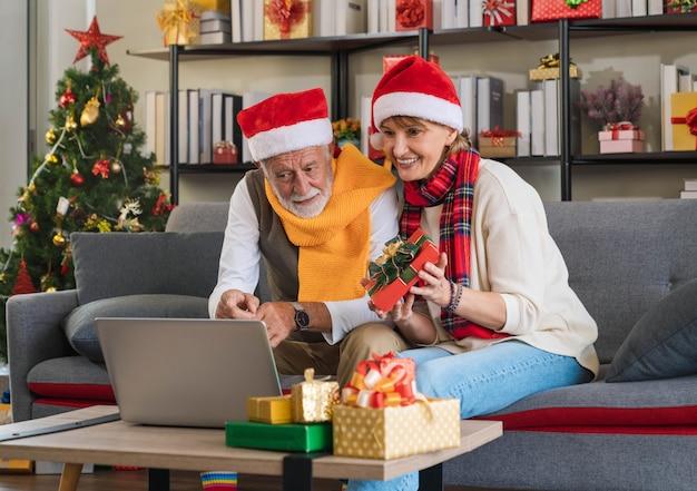 Älteres paar in weihnachtsmütze sitzt auf der couch, die familie online mit laptop-computer anruft, glücklich mit dem erhaltenen geschenk zu hause mit weihnachtsbaum. in den ferien kontakt zu den enkeln halten.