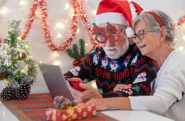 Älteres paar in weihnachtssüßer und weihnachtsmütze bei der verwendung von laptop-computer und handy. älteres ehepaar feiert weihnachtsereignis. frohe weihnachten und ein glückliches neues jahr