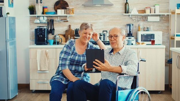 Älteres paar lacht und winkt während eines videoanrufs mit enkelkindern mit tablet-computer in der küche. gelähmter behinderter alter älterer mann mit moderner kommunikationstechnologie.