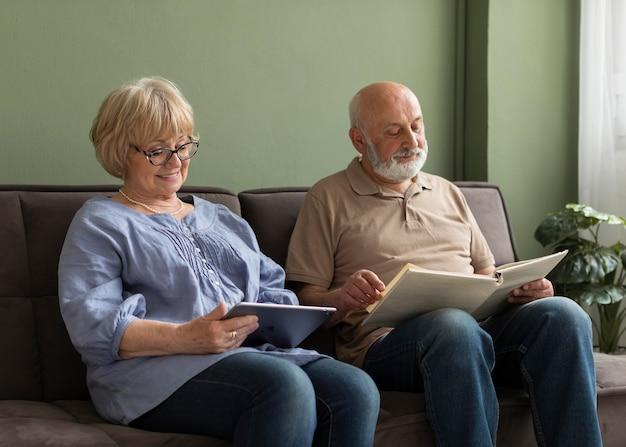 Älteres paar mit buch und tablette