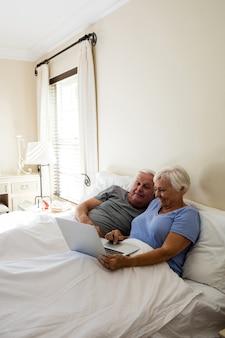Älteres paar mit laptop im schlafzimmer zu hause