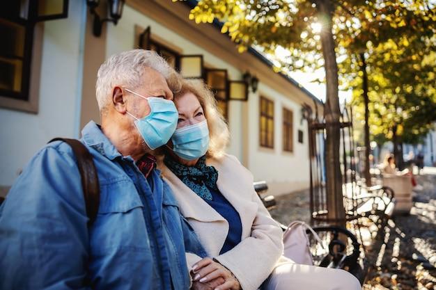 Älteres paar mit masken, die draußen auf der bank sitzen und hände halten.