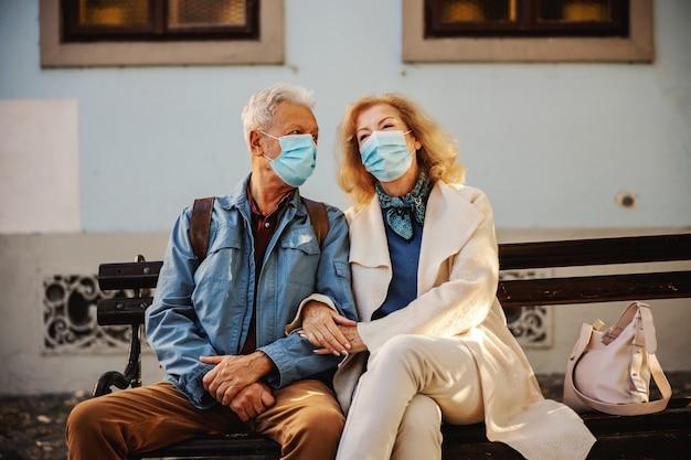 Älteres paar mit masken, die draußen auf der bank sitzen und hände halten