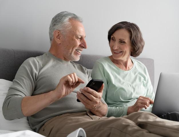 Älteres paar mit mittlerem schuss mit telefon