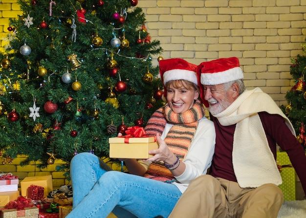 Älteres paar mit weihnachtsmann-hut, das gegenwärtig beim zusammensitzen zusammensitzt und als nächstes verzierten weihnachtsbaum mit glück hält und betrachtet. romantischer winterurlaub.
