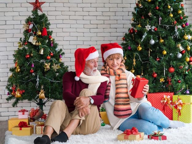 Älteres paar mit weihnachtsmann-hut, das gegenwärtig mit aufgeregtem gesicht beim sitzen des nächsten verzierten weihnachtsbaums im wohnzimmer hält und schaut. überraschungsgeschenk von frau. romantischer winterurlaub.