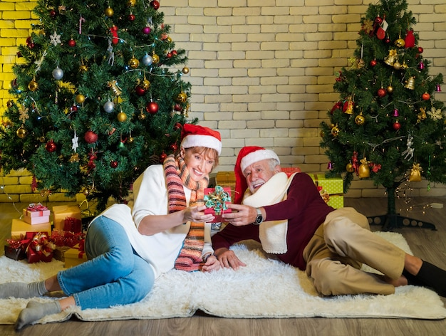 Älteres paar mit weihnachtsmann-hut, das weihnachtsgeschenk hält und betrachtet, während es sich vor dem geschmückten weihnachtsbaum im wohnzimmer niederlegt. frau mit geschenk zufrieden. romantischer winterurlaub.