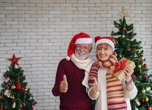Älteres paar mit weihnachtsmann-hut, der geschenkboxlächeln hält und daumen hoch über verziertem weihnachtsbaum und weißem backsteinmauerhintergrund gestikuliert. frohe weihnachten und ein glückliches neues jahr.