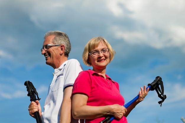 Älteres paar posiert mit nordic walking stöcken