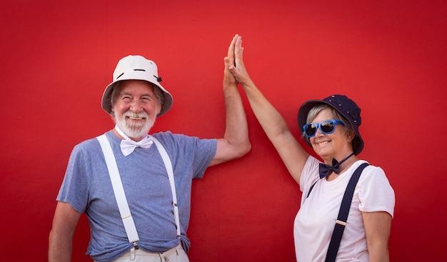 Älteres paar von menschen gegen eine rote wand, die freiheit und urlaub genießen. gekleidet mit bunten mützen, fliegen und hosenträgern. weiße haare und bart für den mann