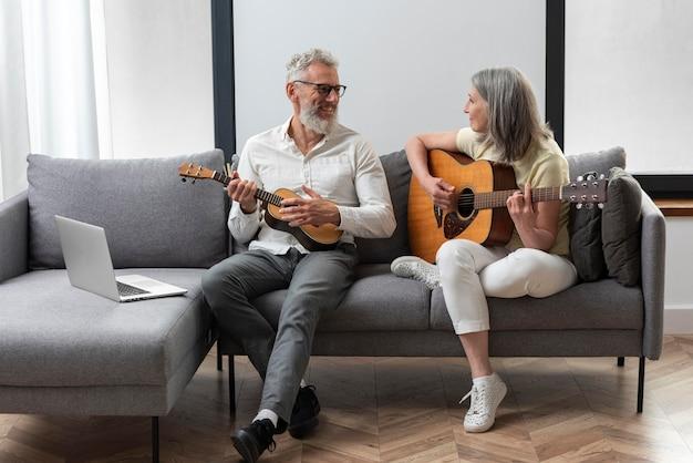 Älteres paar zu hause, das gitarren- und ukuleleunterricht auf dem laptop studiert