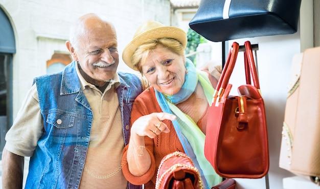 Älteres paareinkaufen am modetaschenspeicher mit der frau, die schaukasten auf ehemann zeigt
