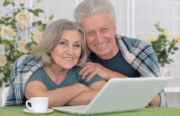 Älteres paarporträt mit laptop zu hause
