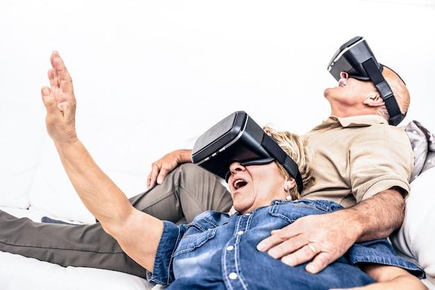 Älteres reifes paar, das spaß zusammen mit dem virtual-reality-headset hat, das auf sofa sitzt
