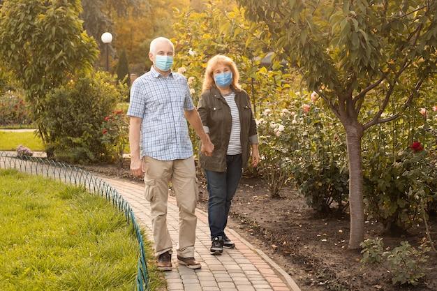 Älteres seniorenpaar, das draußen mit medizinischer maske geht