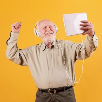 Älteres tanzen des niedrigen winkels und hörende musik