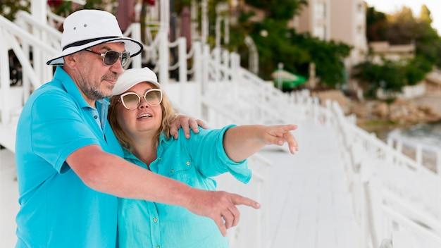 Älteres touristenpaar am strand, das auf etwas zeigt